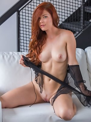 Redhead Mia Sollis, strips her see-through top baring her sexy, curvy body and   delectable pussy on the couch.